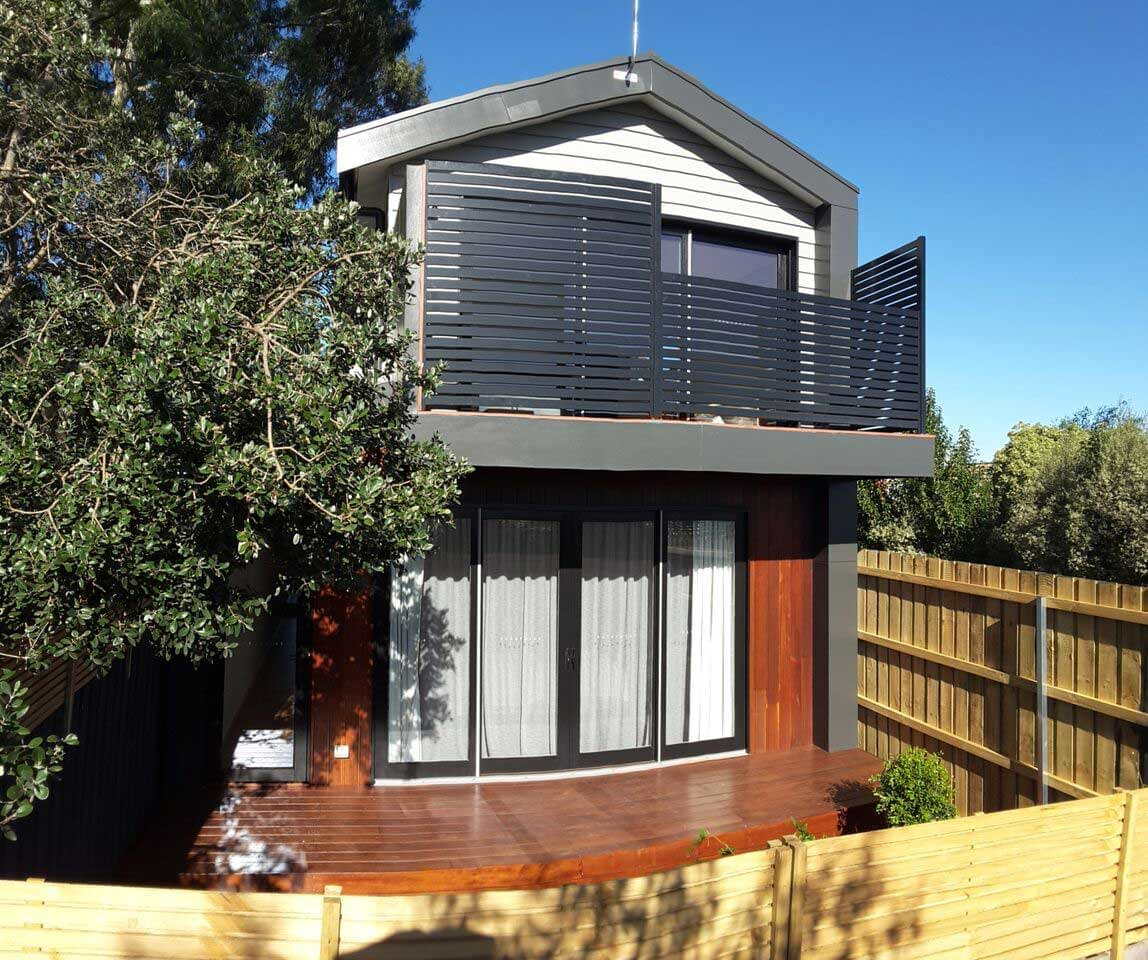 Rear deck second storey extension with timber railing on Glen Iris house by Mass Constructions.