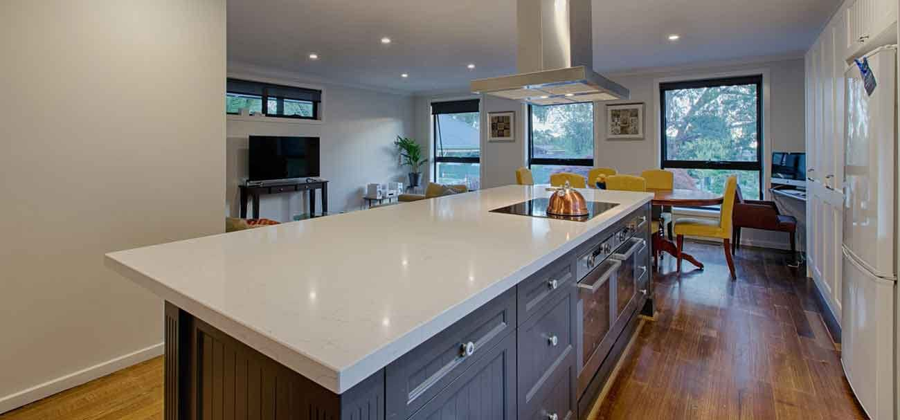 Marble top kitchen island with canopy rangehood in Ferntree Gully.